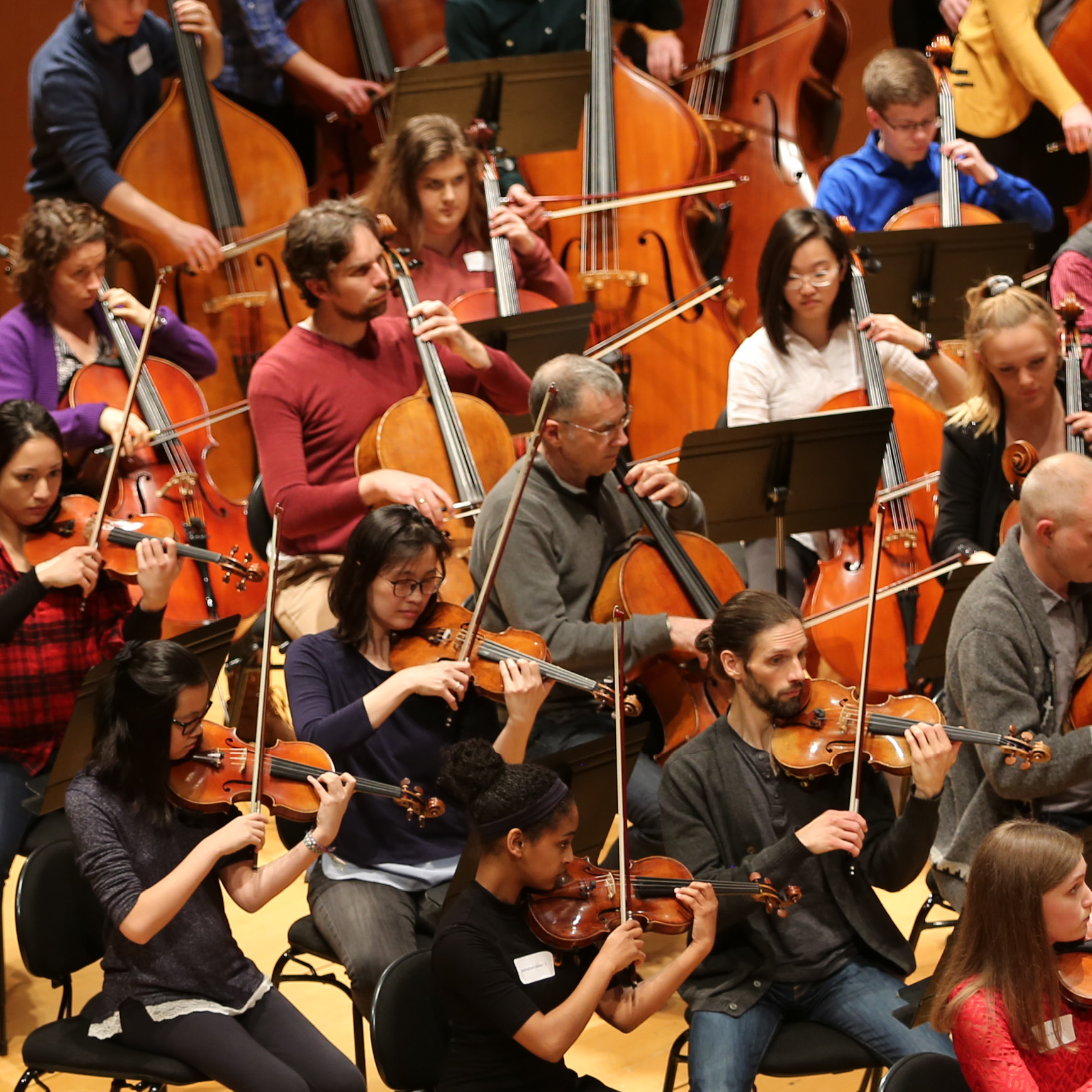 Kansas City Symphony members with Kansas City Youth Symphony members performing side-by-side in Helzberg Hall.