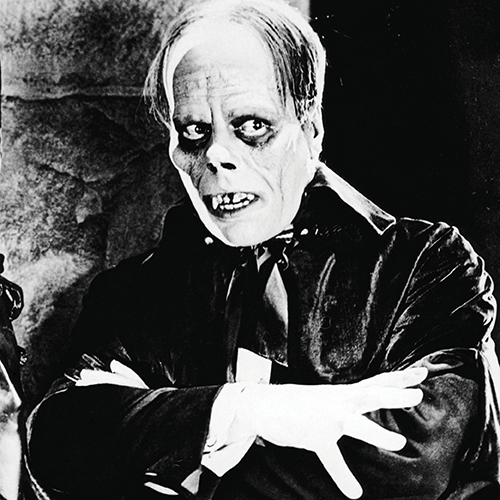 Image of Phantom of the Opera looking off to the right, decaying teeth exposed with arms crossed